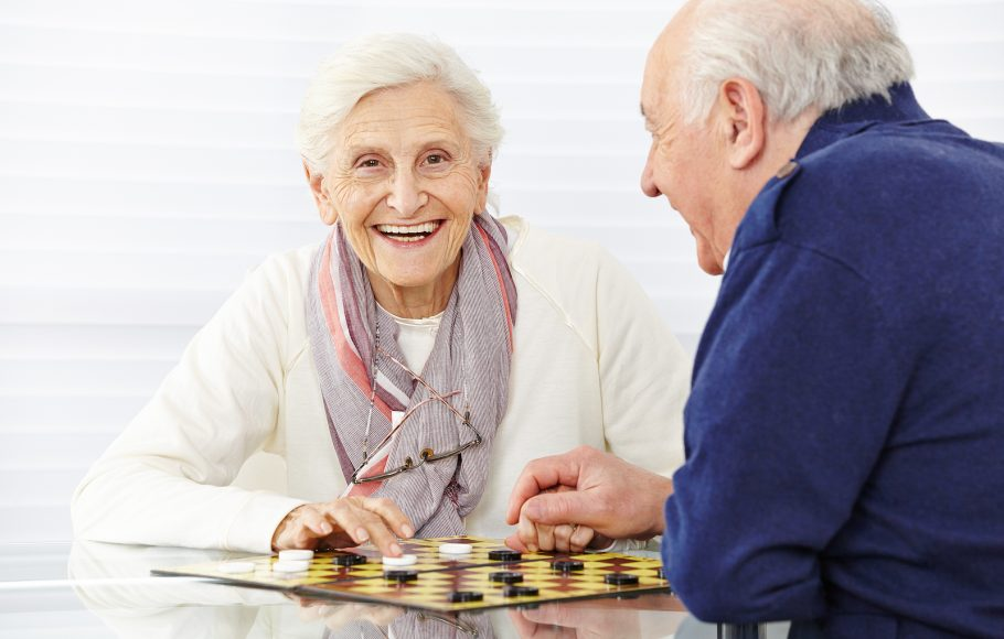 Happy senior couple playing checkers in a retirement home